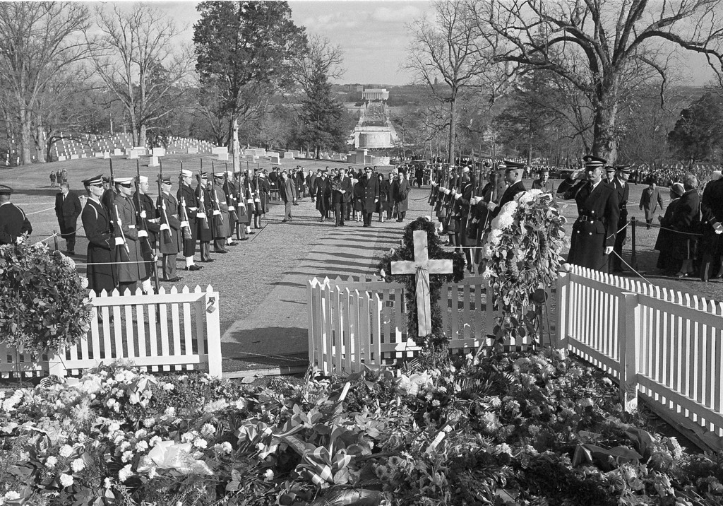 . Men of all services hold their rifles at salute as President Lyndon Johnson carries a bouquet of red roses to Kennedy\'s grave on Dec. 1, 1963. Maj. Gen. Philip C. Wehle, commander of the Military District of Washington, walks with Johnson. Henry Burroughs, Associated Press file