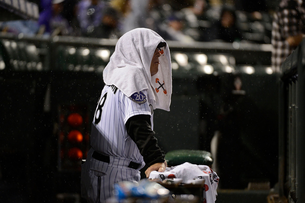 . DENVER, CO. - MAY 07: Rene Lachemann (38) of the Colorado Rockies seeks shelter under a towel as the rain begins to fall in the fifth inning during their game against the New York Yankees May 7, 2013 at Coors Field. (Photo By John Leyba/The Denver Post)