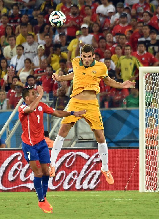 . Chile\'s forward Alexis Sanchez (L) and Australia\'s defender Matthew Spiranovic vie for the ball during a Group B football match between Chile and Australia at the Pantanal Arena in Cuiaba during the 2014 FIFA World Cup on June 13, 2014.     AFP PHOTO / LUIS ACOSTA