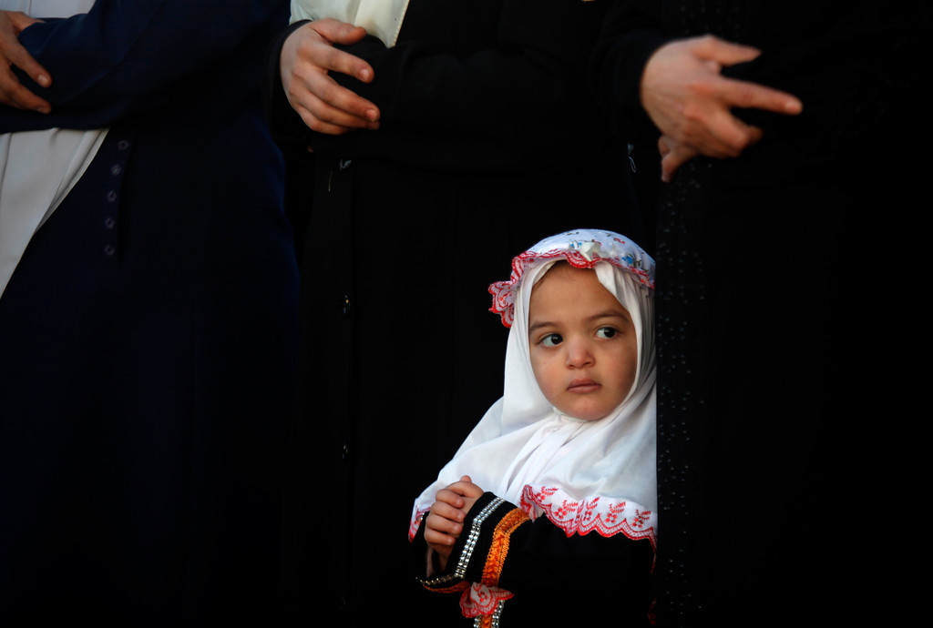 . A young Palestinian girl attends prayers on the first day of  Eid al-Adha at Al-Yarmouk stadium in Gaza City, Tuesday, Oct. 15, 2013. Muslims worldwide are celebrating Eid al-Adha, or the Feast of the Sacrifice on Oct. 15, by sacrificial killing of sheep, goats, cows or camels. The slaughter commemorates the biblical story of Abraham, who was on the verge of sacrificing his son to obey God\'s command, when God interceded by substituting a ram in the child\'s place. (AP Photo/Hatem Moussa)