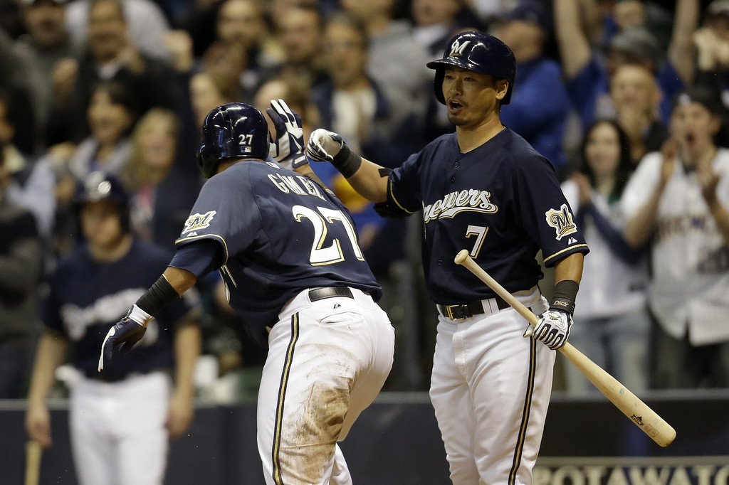 . MILWAUKEE, WI - APRIL 2: Norichika Aoki #7 of the Milwaukee Brewers celebrates with Carlos Gomez #27 after he crosses home plate during the bottom of the second inning against the Colorado Rockies at Miller Park on April 2, 2013 in Milwaukee, Wisconsin. (Photo by Mike McGinnis/Getty Images)