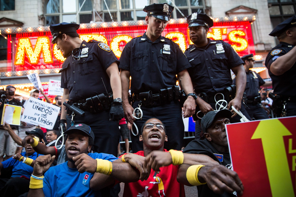 . *** BESTPIX *** NEW YORK, NY - SEPTEMBER 04:  Protesters demanding higher wages and unionization for fast food workers block traffic near Times Square on September 4, 2014 in New York City. Protests are planned in more than 100 cities throughout the U.S. today, as workers demand higher wages.  (Photo by Andrew Burton/Getty Images)