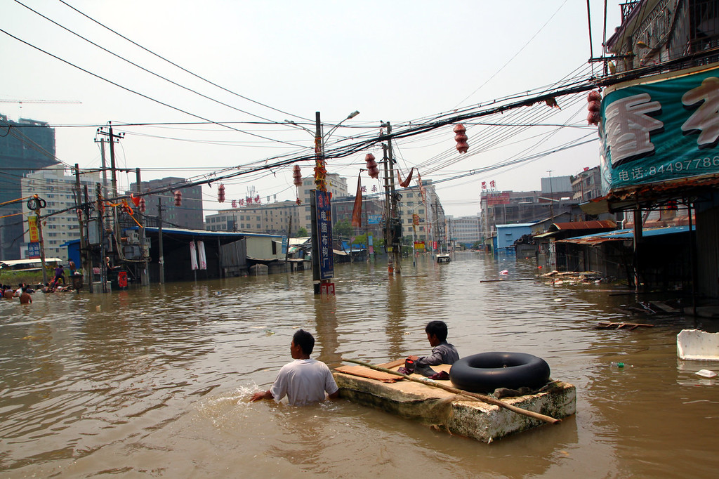 . Residents wade in a flooded street on August 20, 2013 in Shantou, China. 20 people were killed and 7 others missing after typhoon Utor made landfall in Guangdong province on Wednesday.  (Photo by ChinaFotoPress/ChinaFotoPress via Getty Images)