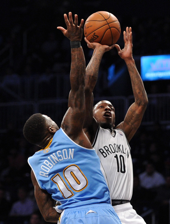 . NEW YORK, NY - DECEMBER 03:  Tyshawn Taylor #10 of the Brooklyn Nets takes a shot over Nate Robinson #10 of the Denver Nuggets during the second half at Barclays Center on December 3, 2013 in the Brooklyn borough of New York City. The Nuggets defeat the Nets 111-87.(Photo by Maddie Meyer/Getty Images)