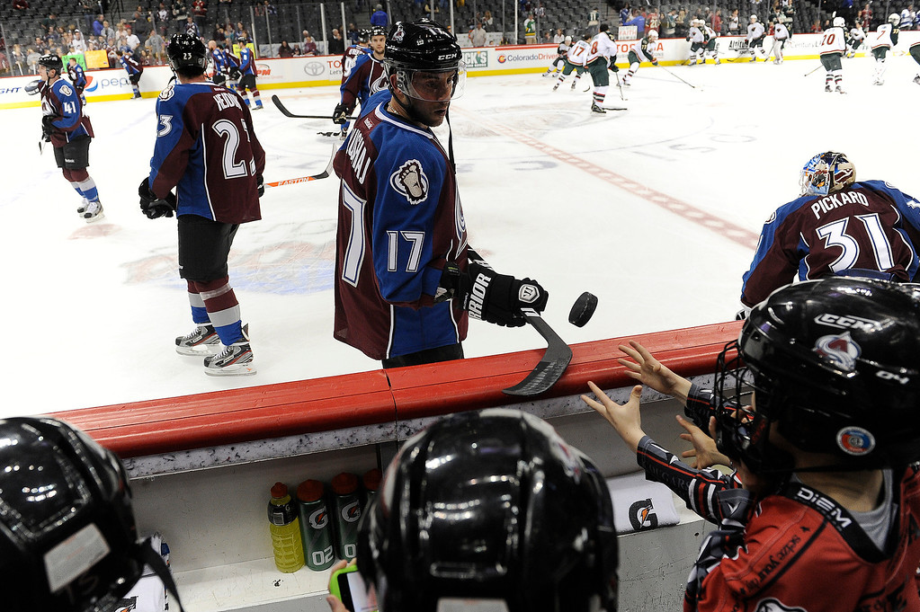. Aaron Palushaj (17) of the Colorado Avalanche flips a practice puck to a young fan on the bench during warm ups prior to their game against the Minnesota Wild on Saturday, April 27, 2012 at Pepsi Center. Seth A. McConnell, The Denver Post