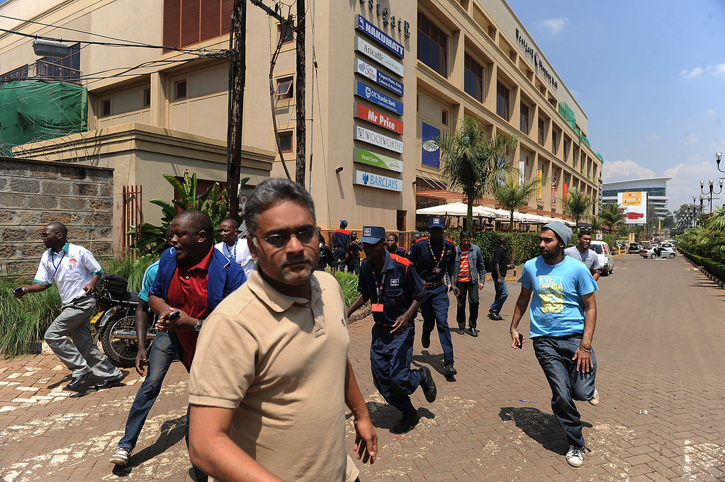 . People run away from an upmarket mall after masked gunmen stormed it and sprayed gunfire on shoppers and staff, killing at least six on September 21, 2013 in Nairobi. The Gunmen have taken at least seven hostages, police and security guards told an AFP reporter at the scene. AFP PHOTO/SIMON MAINA/AFP/Getty Images