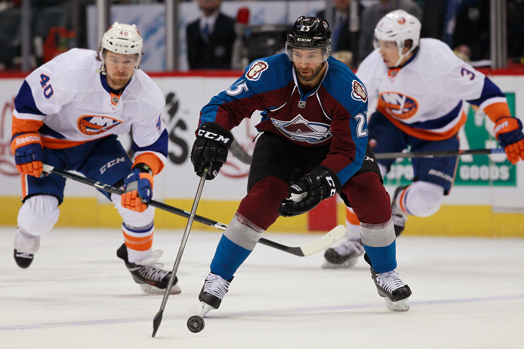 . Colorado Avalanche center Maxime Talbot, front, picks up a loose puck in front of New York Islanders right wing Michael Grabner, left, of Austria, and defenseman Travis Hamonic during the first period of an NHL hockey game in Denver on Friday, Jan. 10, 2014. (AP Photo/David Zalubowski)