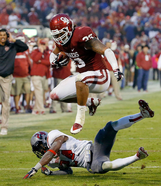 . Oklahoma fullback Trey Millard (33) jumps over Texas Tech defensive back Bruce Jones (24) in the fourth quarter of an NCAA college football game in Norman, Okla., Saturday, Oct. 26, 2013. Oklahoma won 38-30. (AP Photo/Sue Ogrocki)