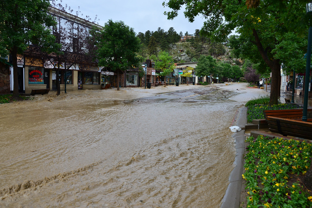 . Floodwater races down Elkhorn Avenue Friday morning, Sept. 13, 2013. John Cordsen/Estes Park Trail-Gazette