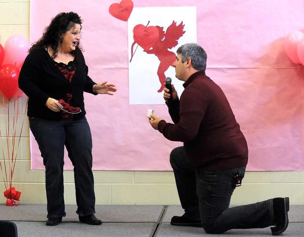 """. Heather Ford, 39, removes her blindfold during a game of \""""pin-the-heart-on-cupid\"""" at the Meadow Lands Elementary School gym, to find her boyfriend, Todd Bevil, 34, down on bended knee with a marriage proposal, Thursday morning, Feb. 14, 2013 in the middle of a school-wide Valentines Day assembly in Owensboro, Ky. They met at a school PTO meeting where she teaches and has children and he has a son more than a year ago. (AP Photo/The Messenger-Inquirer, Gary Emord-Netzley)"""