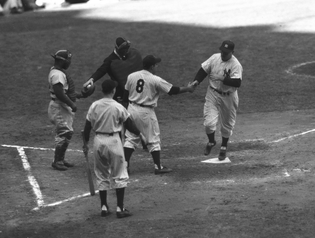 . Yankee first baseman Johnny Mize is greeted with handshake by Yogi Berra (8) as he toes plate on fourth inning homer in fourth game of the World Series at Yankee Stadium, New York, Oct. 4, 1952. It was Mizes second four-bagger of the series. Yankee batboy waits to greet big John as Dodger catcher Roy Campanella gets a new ball from plate umpire Bill Mckinley. Yanks won, 2 to 0, and evened series at 2-2. (AP Photo)