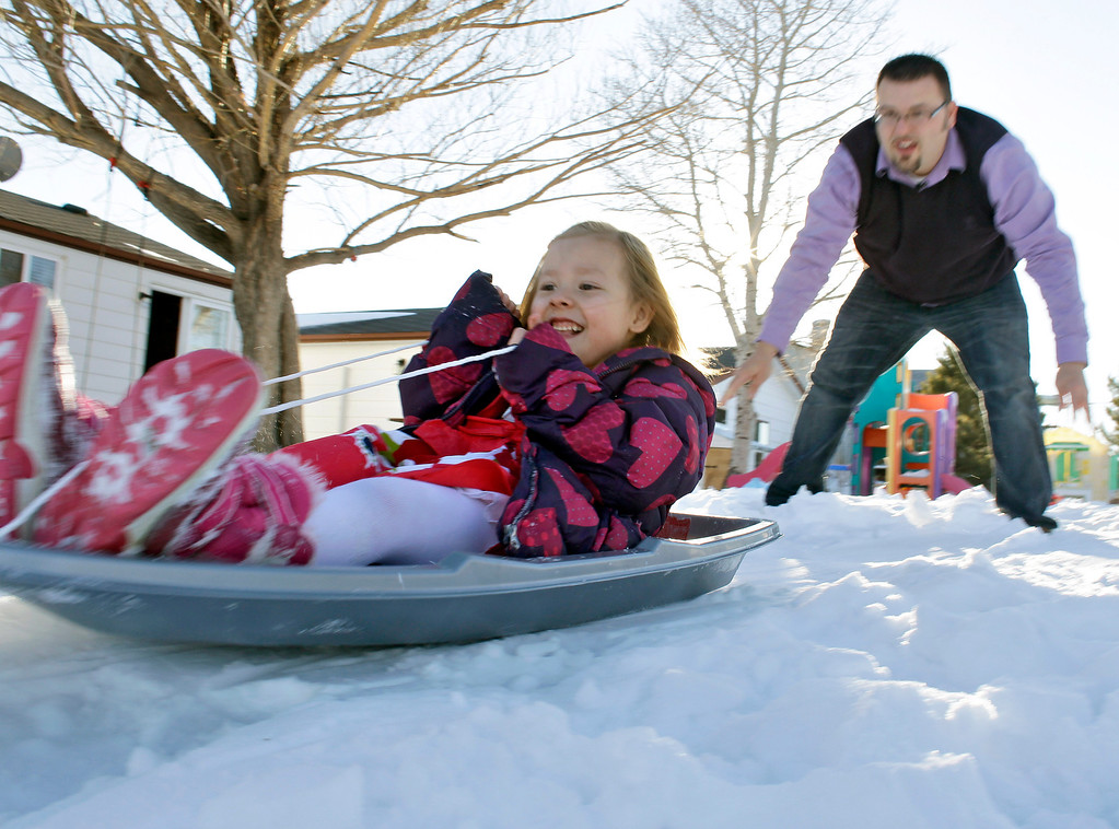 . In this Monday, Feb. 25, 2013, photo, Coy Mathis is pushed on a sled by her father, Jeremy, in the back yard of their home in Fountain, Colo.  (AP Photo/Brennan Linsley)