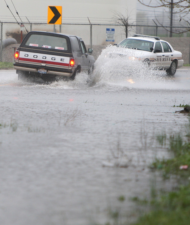 . A driver splashes his way past a Madison County, Ill., Deputy Sheriff on the curve of Old Edwardsville Road in Roxana, Ill., Thursday, April 18, 2013, near Thomas Street just before Roxana Police called for barricades to close the road.  (AP Photo/The Telegraph, John Badman)