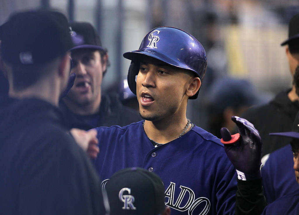 . Carlos Gonzalez #5 of the Colorado Rockies celebrates his first inning home run in the dugout with teammates against the Los Angeles Dodgers during the MLB game at Dodger Stadium on April 30, 2013 in Los Angeles, California.  (Photo by Victor Decolongon/Getty Images)