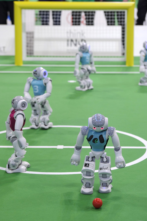 . Two teams of robots play against each other in the 2014 RoboCup German Open tournament on April 03, 2014 in Magdeburg, Germany. The robots, which are models called Nao, manufactured by Aldebaran Robotics, perform autonomously and communicate with one another via WLAN. 950 participants from 12 countries are participating in the the three-day tournament that compete in a variety of disciplines, including soccer, rescue and dance. (Photo by Jens Schlueter/Getty Images)