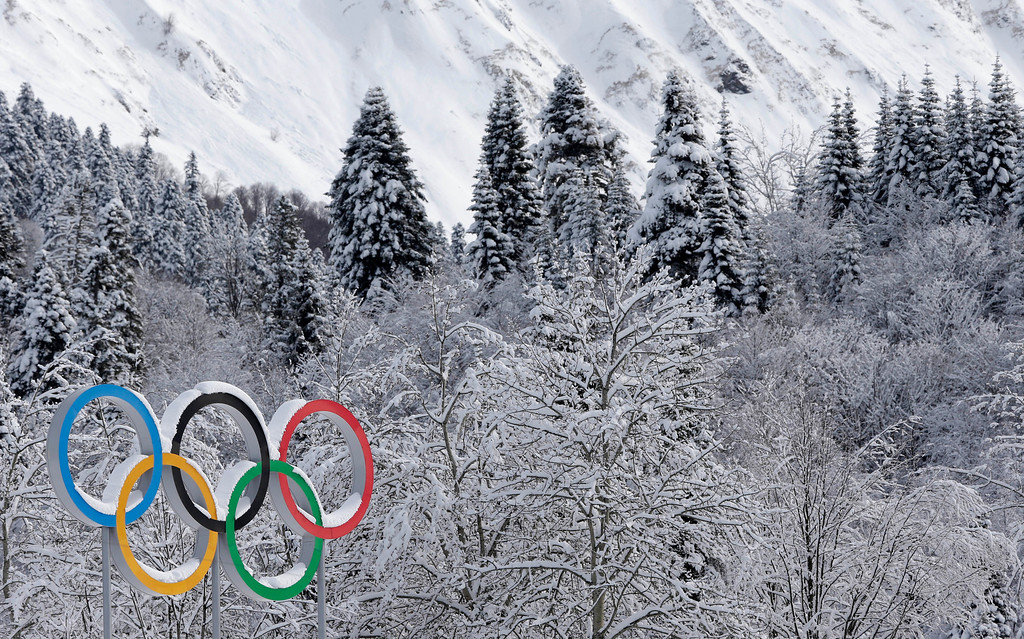 . The Olympic rings are covered with freshly fallen snow prior to the cross-country sprint competitions at the 2014 Winter Olympics, Wednesday, Feb. 19, 2014, in Krasnaya Polyana, Russia. (AP Photo/Matthias Schrader)