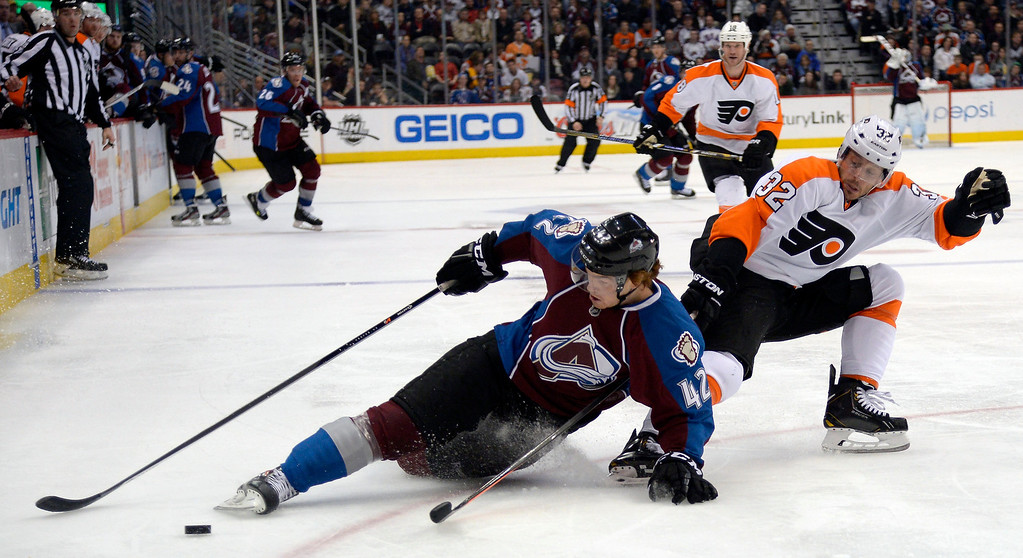 . Colorado Avalanche center Brad Malone (42) loses an edge as he falls to the ice going after the puck with Philadelphia Flyers defenseman Mark Streit (32) during the third period January 2, 2014 at Pepsi Center. (Photo by John Leyba/The Denver Post)