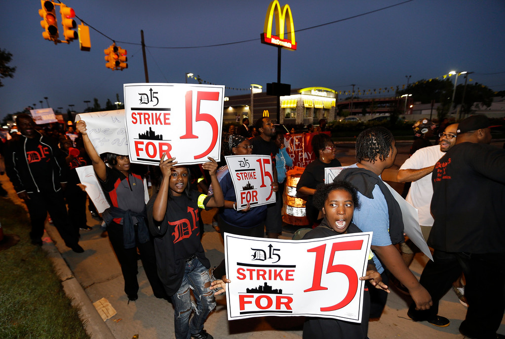 . Protesters march on a McDonalds restaurant in Detroit as part of a national protest to push fast-food chains to pay their employees at least $15 an hour Thursday, Sept. 4, 2014. Hundreds of workers from McDonald\'s, Taco Bell, Wendy\'s and other fast-food chains are expected to walk off their jobs Thursday, according to labor organizers. (AP Photo/Paul Sancya)