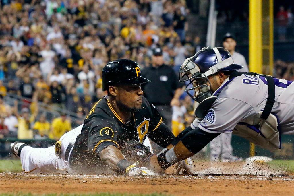 . Pittsburgh Pirates\' Starling Marte, left, is tagged out attempting an inside the park home run by Colorado Rockies catcher Wilin Rosario during the sixth inning of a baseball game in Pittsburgh Friday, July 18, 2014. Marte drove in a run on the play. (AP Photo/Gene J. Puskar)