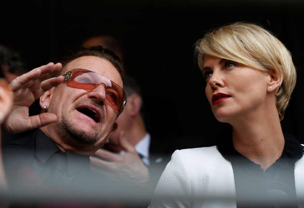 . Actress Charlize Theron speaks with musician Bono before the memorial service for former South African president Nelson Mandela at the FNB Stadium in Soweto near Johannesburg, Tuesday, Dec. 10, 2013. (AP Photo/Ben Curtis)