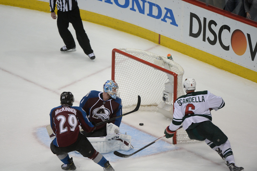 . Marco Scandella (6) of the Minnesota Wild scores a shorthanded goal past Semyon Varlamov (1) and Nathan MacKinnon (29) of the Colorado Avalanche during the third period of action. The Colorado Avalanche hosted the Minnesota Wild in the first round of the Stanley Cup Playoffs at the Pepsi Center in Denver, Colorado on Saturday, April 19, 2014. (Photo by Karl Gehring/The Denver Post)