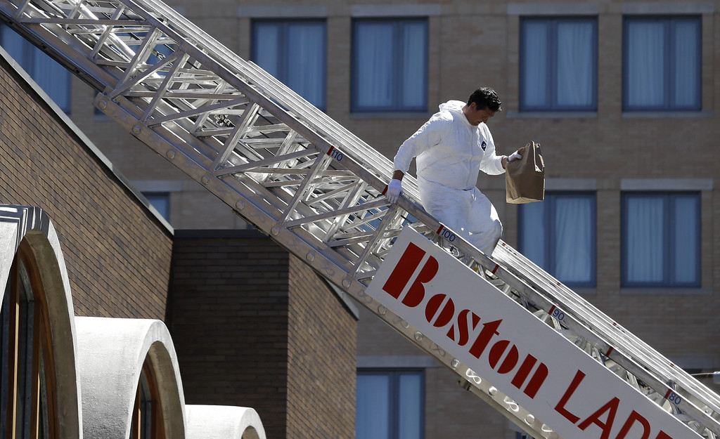 . An FBI investigator walks down a fire truck ladder with a bag from the top of a building at the corner of Boylston Street and Fairfield Street Wednesday April 17, 2013, in Boston. Investigators in white jumpsuits fanned out across the streets, rooftops and awnings around the blast site in search of clues on Wednesday. (AP Photo/Julio Cortez)
