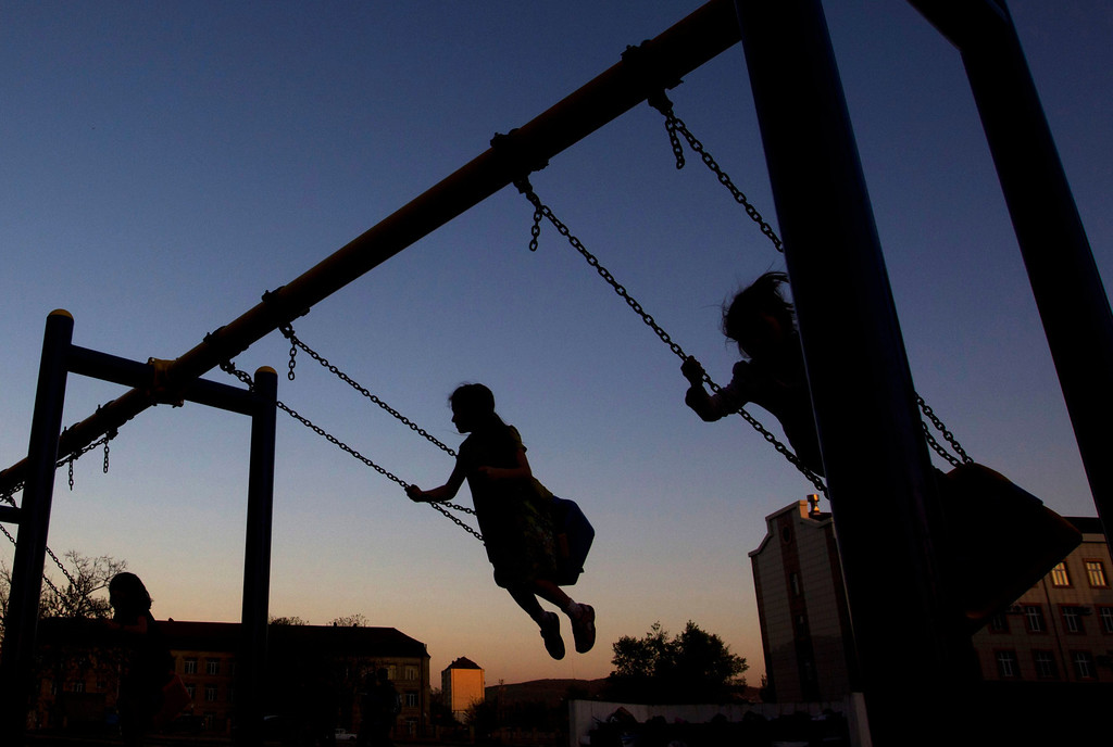 . Girls play on swings in a playground in the Chechen capital Grozny April 29, 2013. The naming of two Chechens, Dzhokhar and Tamerlan Tsarnaev, as suspects in the Boston Marathon bombings has put Chechnya - the former site of a bloody separatist insurgency - back on the world\'s front pages. Chechnya appears almost miraculously reborn. The streets have been rebuilt. Walls riddled with bullet holes are long gone. New high rise buildings soar into the sky. Spotless playgrounds are packed with children. A giant marble mosque glimmers in the night. Yet, scratch the surface and the miracle is less impressive than it seems. Behind closed doors, people speak of a warped and oppressive place, run by a Kremlin-imposed leader through fear.  Picture taken April 29, 2013.   REUTERS/Maxim Shemetov