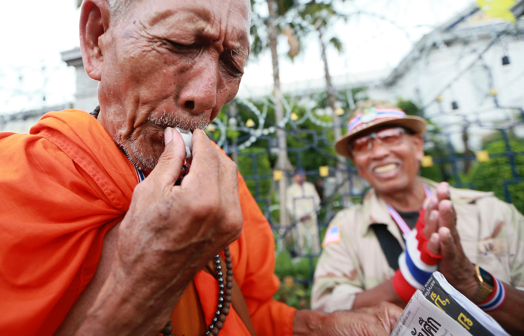 . A Thai Buddhist monk blows a whistle during a rally outside Interior Ministry in Bangkok, Thailand, Tuesday, Nov. 26, 2013.  (AP Photo/Wason Wanichakorn)