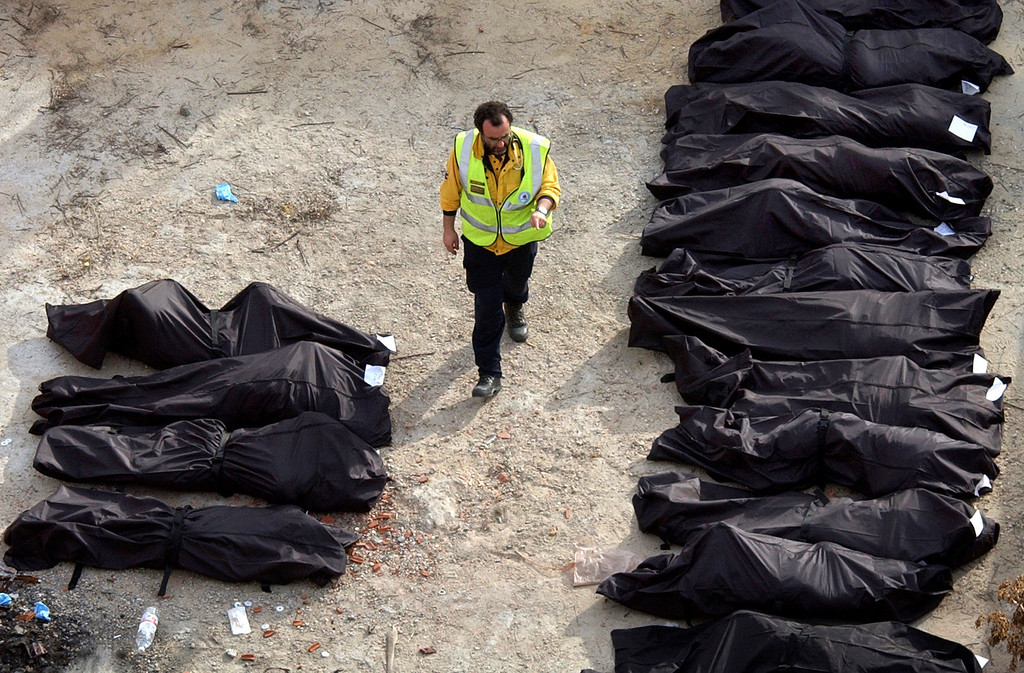 . A Spanish rescue worker counts the bodies removed from one of the commuter trains following a number of explosions on trains in Madrid, in this March 11, 2004, photo. A Spanish judge on Tuesday, April 11, 2006, handed down the first indictments in the Madrid train bombings of 2004, charging 29 people with murder, terrorism or other crimes after a two-year probe. (AP Photo/Peter DeJong)