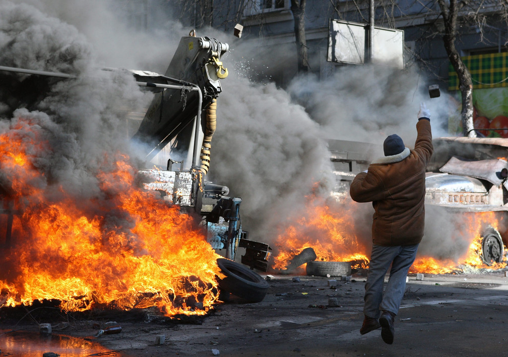 . A protester throws stones at riot police during the continuing protest in downtown Kiev, Ukraine, 18 February 2014.  EPA/IGOR KOVALENKO