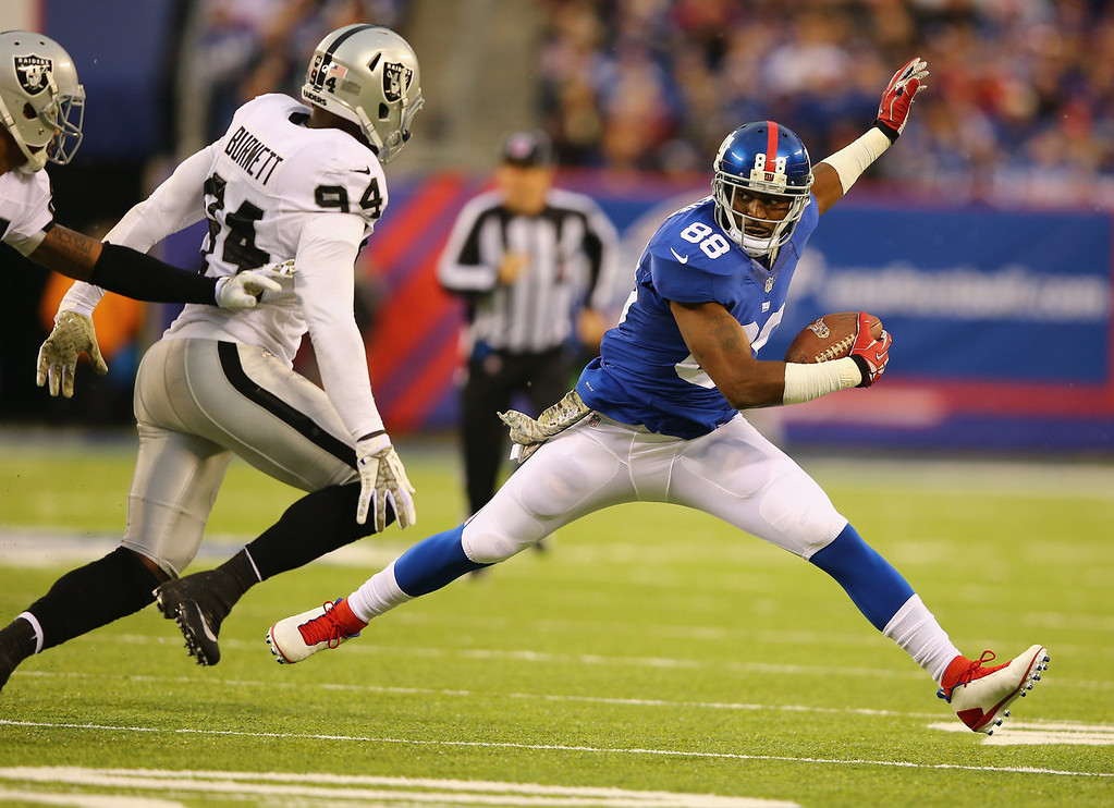 . Hakeem Nicks #88 of the New York Giants  runs after a catch against  Kevin Burnett #94 of the Oakland Raiders during their game at MetLife Stadium on November 10, 2013 in East Rutherford, New Jersey.  (Photo by Al Bello/Getty Images)