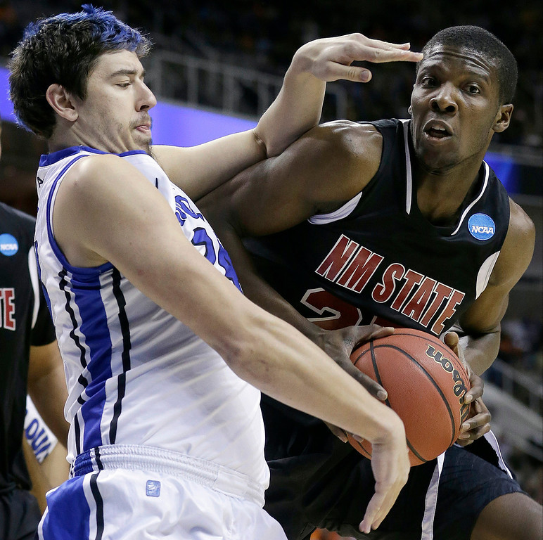. New Mexico State forward Renaldo Dixon, right, grabs a rebound in front of Saint Louis forward Cody Ellis during the first half of a second-round game in the NCAA college basketball tournament in San Jose, Calif., Thursday, March 21, 2013. (AP Photo/Jeff Chiu)