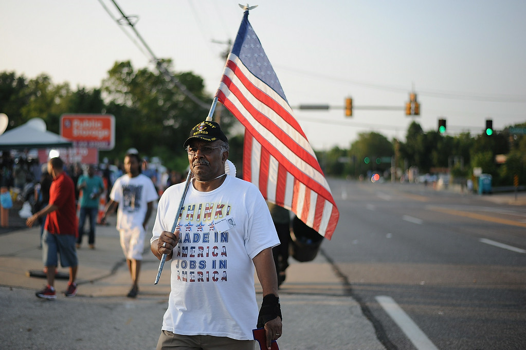 ". Protestors walk during a peaceful protest on West Florissant Ave. in Ferguson, Missouri on August 19, 2014.  Police in the US city of St. Louis shot dead another suspect on Tuesday, a short distance from a suburb that is the scene of protests over the killing of an unarmed black teenager.  St. Louis Police Chief Sam Dotson said in a tweet that officers had responded to a call and found an apparently agitated man, armed with a knife who yelled ""kill me now\"" and approached the patrol.     Michael B. Thomas/AFP/Getty Images"