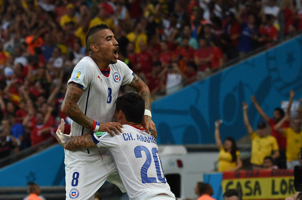 . Chile\'s midfielder Charles Aranguiz (R) celebrates scoring with his teammate midfielder Arturo Vidal during a Group B football match between Spain and Chile in the Maracana Stadium in Rio de Janeiro during the 2014 FIFA World Cup on June 18, 2014. CHRISTOPHE SIMON/AFP/Getty Images