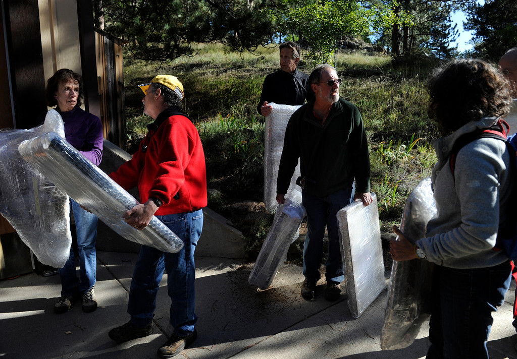 . BOULDER, CO - Sept. 28: Marco Montanari, second from right, gathers his friends and his paintings outside his studio for the hike down hill. Friends and fellow Boulder artists gather to hike in to the home and studio of artist Marco Montanari to rescue and carry out his Encaustic paintings that need to be packed and sent to New York for a show in November. Montanari\'s home and studio did not suffer damage in the floods, but all roads leading in and out had been impassable up until just a few days ago. The group was able to drive a short distance up Wagon Wheel Gap Road and hiked the rest of the way in and out. (Photo By Kathryn Scott Osler/The Denver Post)