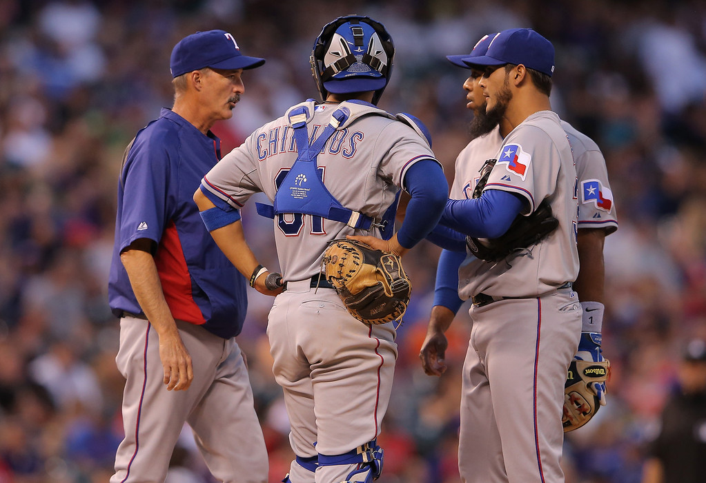. Pitching coach Mike Maddux #31 of the Texas Rangers visits the mound to talk to starting pitcher Martin Perez #33 of the Texas Rangers along with catcher Robinson Chirinos #61 and shortstop Elvis Andrus #1 of the Texas Rangers as they face the Colorado Rockies during Interleague play at Coors Field on May 5, 2014 in Denver, Colorado.  (Photo by Doug Pensinger/Getty Images)