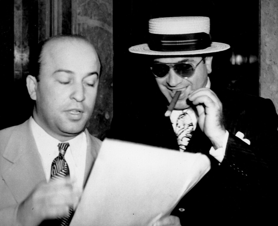 . Al Capone, smoking a cigar, listens as his attorney Abe Teitelbaum explains the legal phases of the government\'s $201,347 tax case against Capone at the Internal Revenue Offices in Miami, Fla. on Feb. 17, 1941.  Capone spent seven years in a federal penitentiary for his civil liability for income tax evasion.  (AP Photo)
