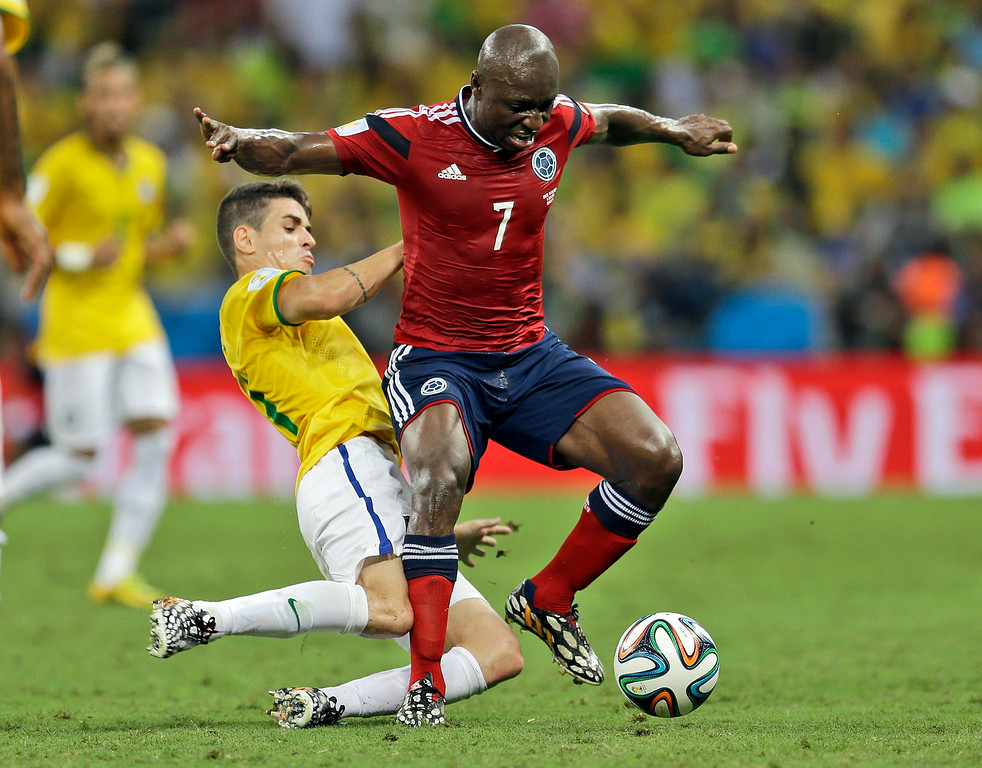 . Brazil\'s Oscar slide tackles Colombia\'s Pablo Armero to clear the ball during the World Cup quarterfinal soccer match between Brazil and Colombia at the Arena Castelao in Fortaleza, Brazil, Friday, July 4, 2014. (AP Photo/Natacha Pisarenko)