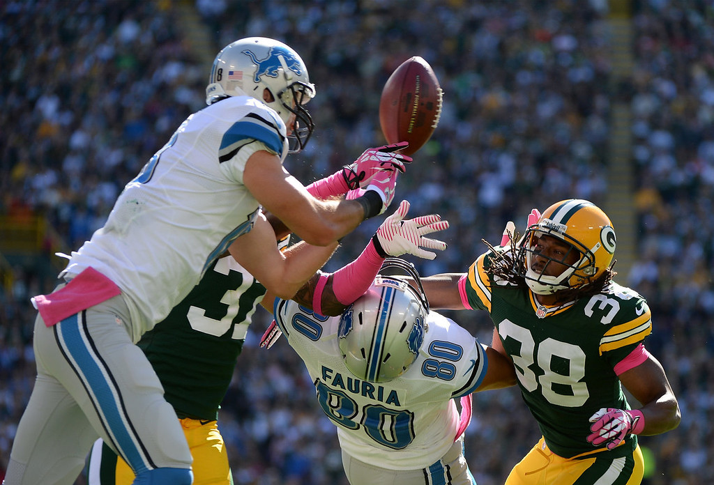 . Micah Hyde #33 of the Green Bay Packers breaks up a pass in front of Joseph Fauria #80 and Kris Durham #18 of the Detroit Lions during the second quarter at Lambeau Field on October 6, 2013 in Green Bay, Wisconsin.  (Photo by Harry How/Getty Images)