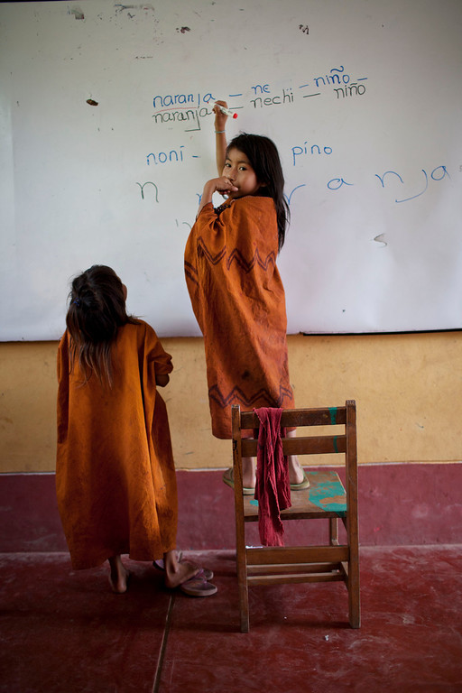 . In this Oct. 1, 2013 photo, Ashaninka Indian girls attend a public school in the Kinkibiri village, Pichari district, Peru. Ashaninka elders teach the new generations to appreciate the wilderness that sustained their ancestors, but many have given up on rainforest life and moved to cities. Elders also worry that their language, a member of the Arawak family, is disappearing. Area schools teach in Spanish. (AP Photo/Rodrigo Abd)