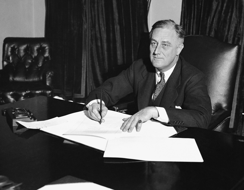 """. At a desk in the cabinet room President Franklin D. Roosevelt signs the Cullen-Harrison Act, or \""""Beer Bill\"""", the first relaxation of the Volstead Act in all the years of prohibition, March 22, 1933, in Washington. With its signature, the new law will permit the sale of beer and wine containing 3.2% alcohol from midnight of April 6. (AP Photo)"""
