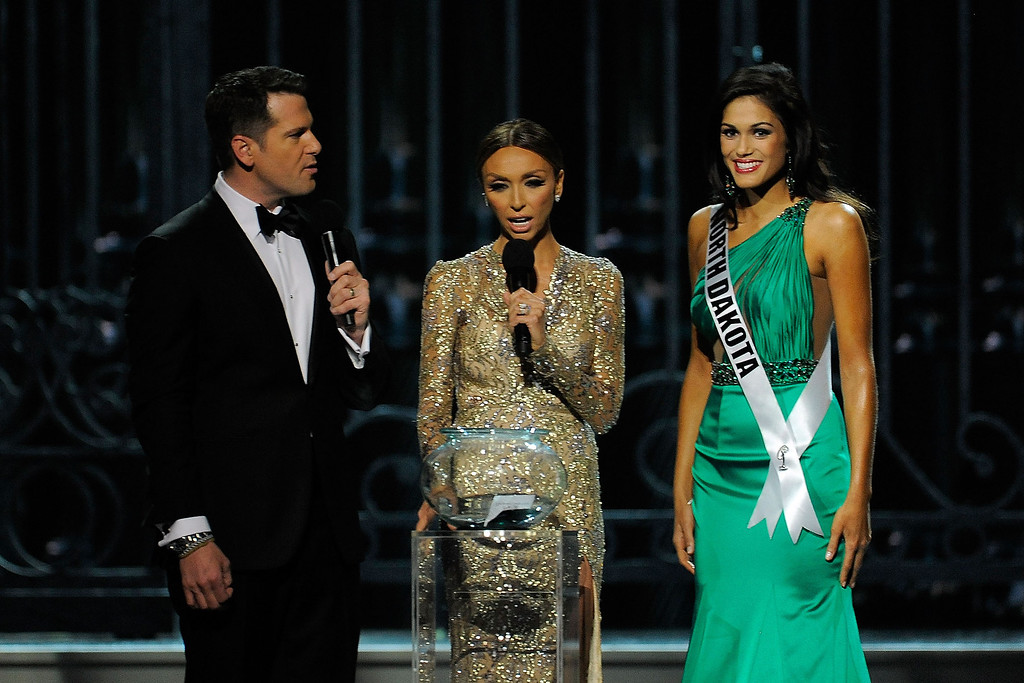 . Hosts Thomas Roberts (L) and Giuliana Rancic (center) speak with Miss North Dakota USA Audra Mari (R) during the 2014 Miss USA Competition at The Baton Rouge River Center on June 8, 2014 in Baton Rouge, Louisiana.  (Photo by Stacy Revere/Getty Images)