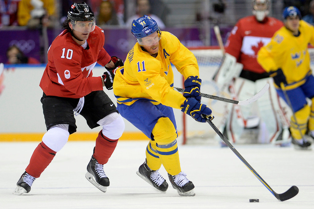 . Daniel Alfredsson (11) of Sweden reaches for the puck as Patrick Sharp (10) of Canada defends during the first period of the men\'s ice hockey gold medal game. Sochi 2014 Winter Olympics on Sunday, February 23, 2014 at Bolshoy Ice Arena. (Photo by AAron Ontiveroz/ The Denver Post)