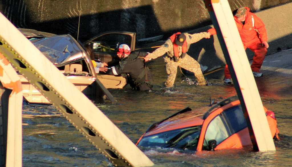 . In this photo provided by Francisco Rodriguez, rescue workers form a human chain as they begin to remove a woman who reaches out from a smashed pickup truck that fell into the Skagit River after the collapse of the Interstate 5 bridgeThursday, May 23, 2013, in Mount Vernon, Wash. (AP Photo/Francisco Rodriguez)