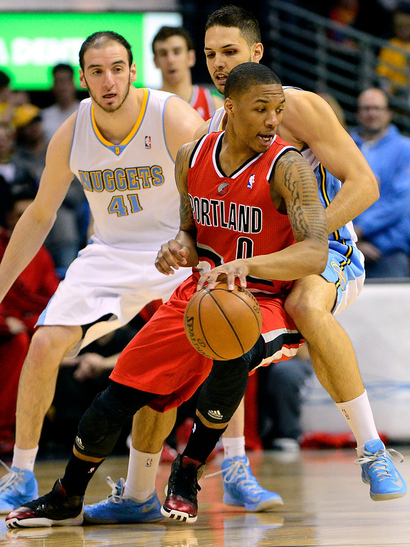 . DENVER, CO - APRIL 14: Evan Fournier (94) of the Denver Nuggets defends Damian Lillard (0) of the Portland Trail Blazers during the first half of action. The Denver Nuggets play the Portland Trail Blazers at the Pepsi Center. (Photo by AAron Ontiveroz/The Denver Post)