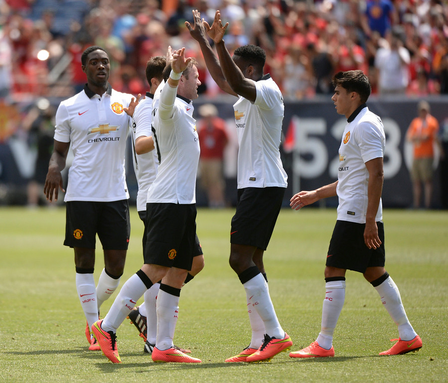. Teammates congratulated Wayne Rooney following his first goal in the first half. Manchester United took on AS Roma in an exhibition soccer game at Sports Authority Field in Denver Saturday afternoon, July 27, 2014. Photo by Karl Gehring/The Denver Post