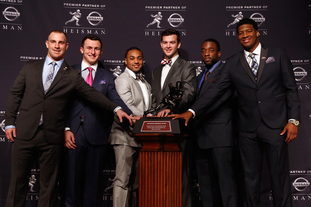. (L-R) Jordan Lynch, quarterback of the Northern Illinios Huskies, Johnny Manziel, quarterback of the Texas A&M aggies, Tre Mason, running back for the Auburn University Tigers, AJ McCarron of the Alabama Crimson Tide, Andre Williams, quarterback of the Boston College Eagles, and Jameis Winston, quarterback of the Florida State Seminoles, pose with the Heisman Trophy prior to the 2013 Heisman Trophy Presentation at the Marriott Marquis on December 14, 2013 in New York City.  (Photo by Jeff Zelevansky/Getty Images)
