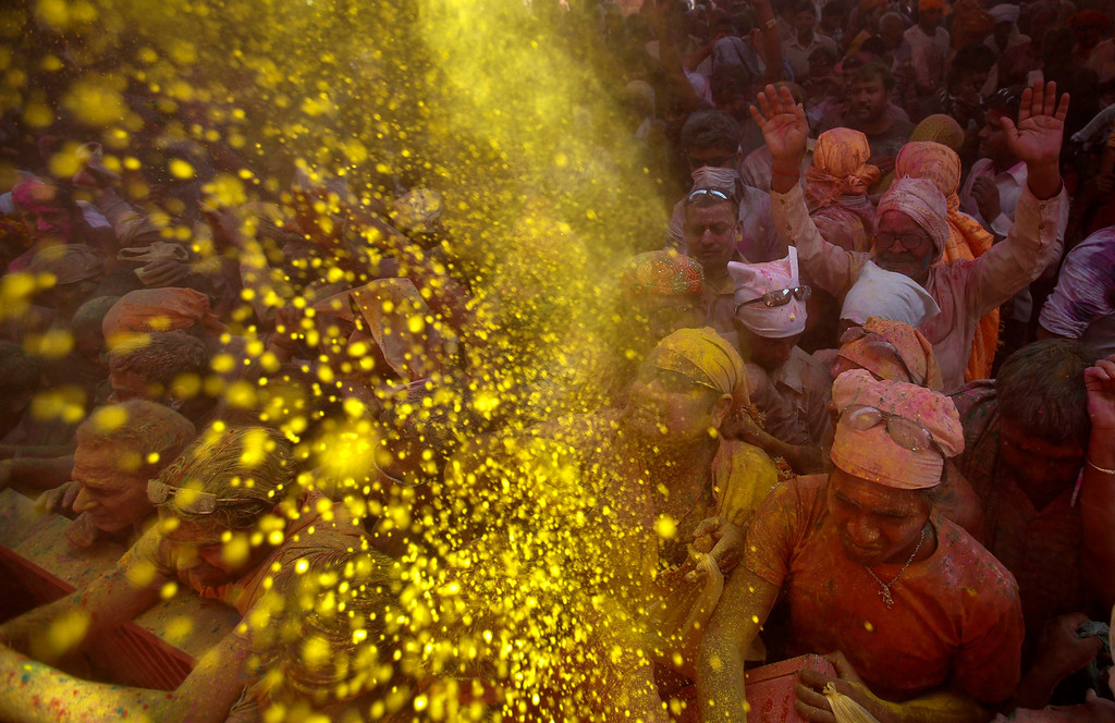 ". Hindu devotees throw coloured powder at a temple during ""Lathmar Holi\"" at the village of Barsana in the northern Indian state of Uttar Pradesh March 21, 2013. In a Holi tradition unique to Barsana and Nandgaon villages, men sing provocative songs to gain the attention of women, who then \""beat\"" them with bamboo sticks called \""lathis\"". Holi, also known as the Festival of Colours, heralds the beginning of spring and is celebrated all over India. REUTERS/Vivek Prakash"