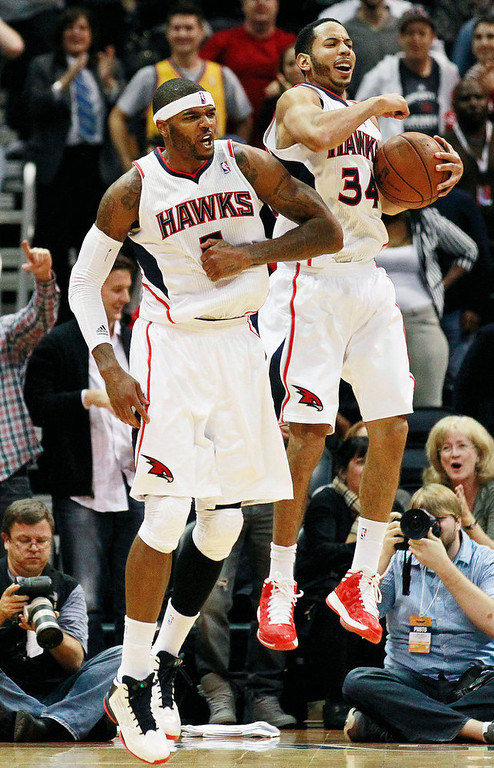 . Atlanta Hawks\' Devin Harris (34) and Josh Smith (5) celebrate in the final seconds of an NBA basketball game against the Denver Nuggets, Wednesday, Dec. 5, 2012, in Atlanta. Atlanta won 108-104. (AP Photo/John Bazemore)
