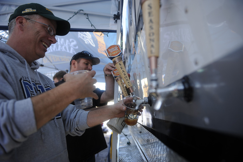 . DENVER, CO: Sept 28, 2013  David Swain pours a beer for one of the many customers standing in the line at Denver\'s Oktoberfest.     (Photo By Erin Hull/The Denver Post)